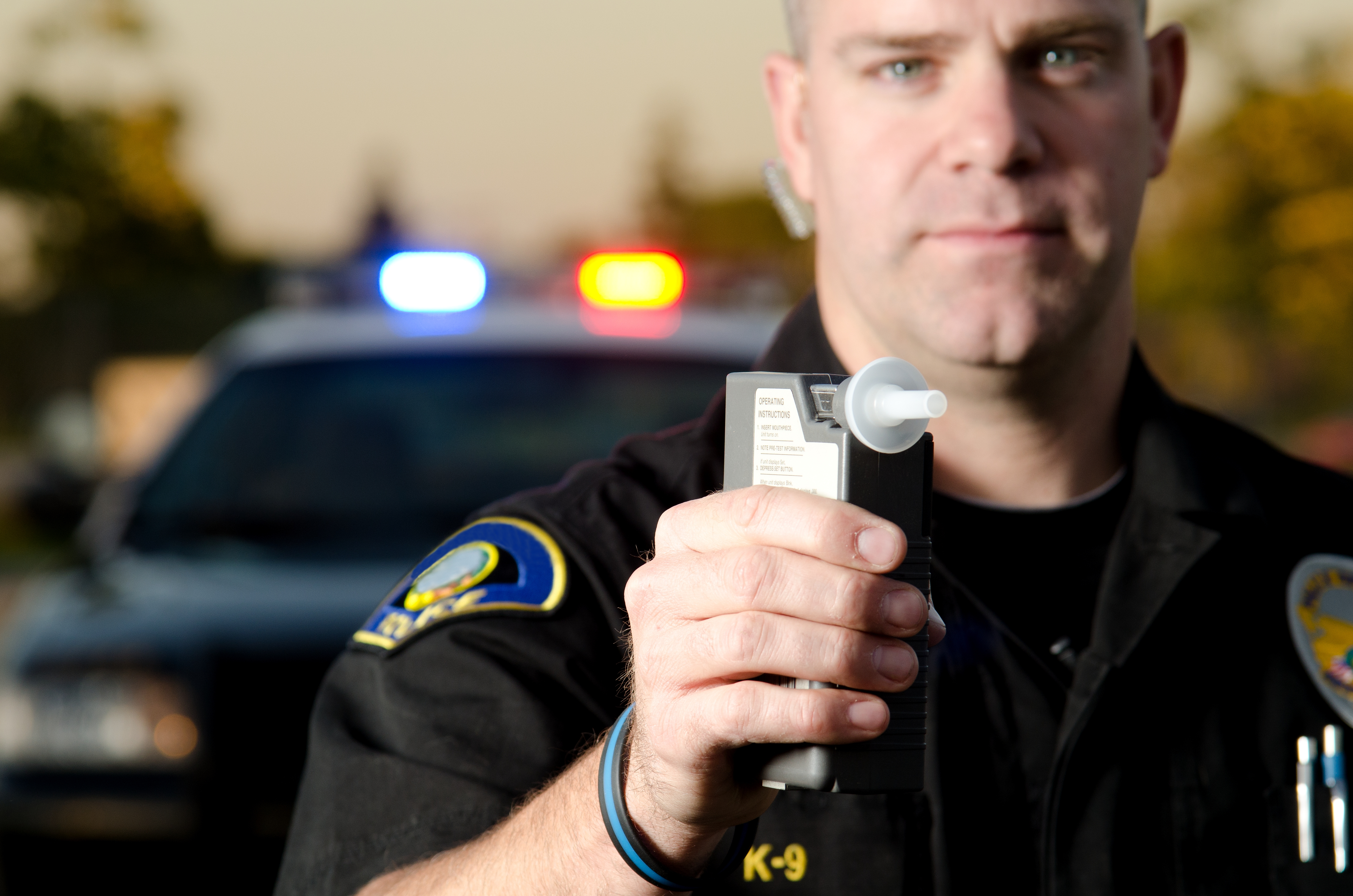 A police officer holding a breath test machine with his police car in the background. *the officer was blurred on purpose.